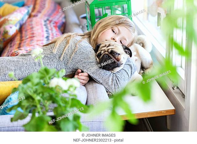 Girl hugging pug dog in living room