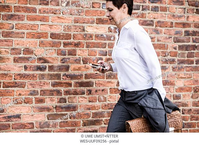 Businesswoman with briefcase and cell phone running in front of brick wall