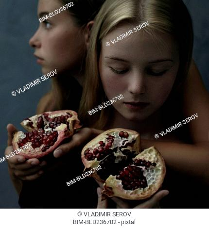 Intertwined Caucasian girls holding sliced pomegranate