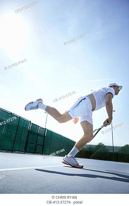 Young male tennis player playing tennis, swinging racket on sunny tennis court