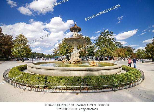 Fountain, and tourist in the background at famous touristic El Retiro park in Madrid, Spain