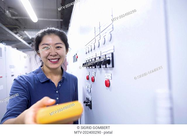 Young female engineer examining control panel with multimeter in an industrial plant, Freiburg im Breisgau, Baden-Württemberg, Germany