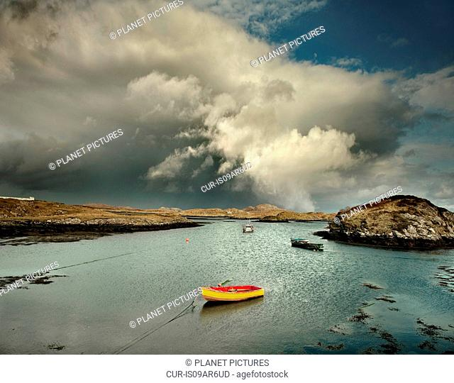 Boats moored in natural sea harbor with storm clouds, Isle of Barra, Hebrides, Scotland, UK