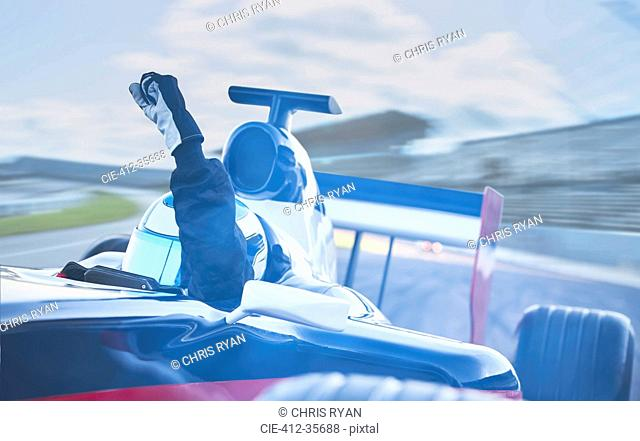 Formula one race car driver cheering, gesturing with fist on sports track