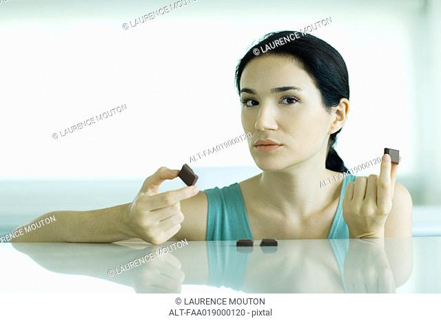 Woman holding up pieces of chocolate