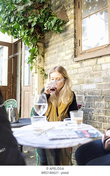 Young woman drinking coffee at outdoor cafe
