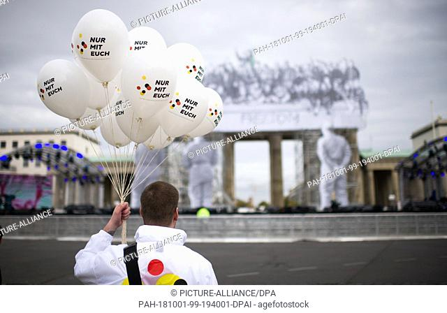 "01 October 2018, Bremen: A man holds balloons with the inscription """"Nur mit Euch"""" (Only with you), the motto of the event"