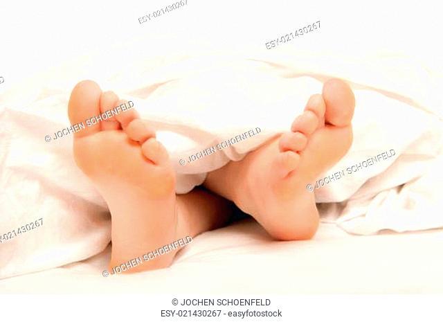Füße einer jungen Frau unter der Bettdecke, Nahaufnahme