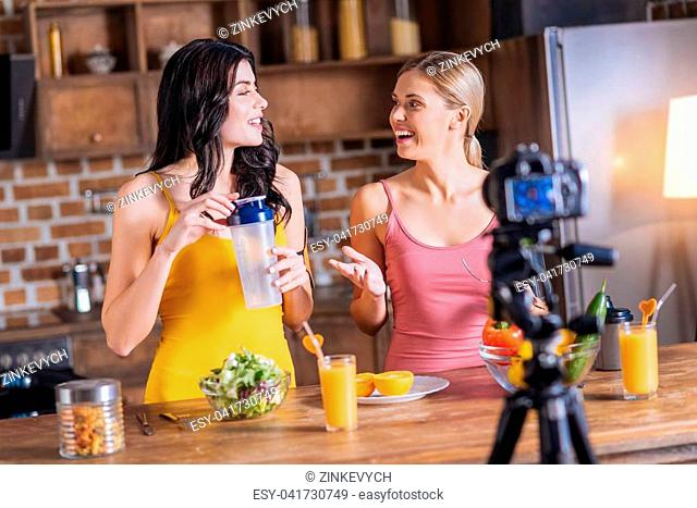 Female bloggers. Positive cheerful healthy women looking at each other and smiling while recording a video together