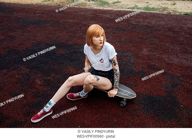 Cool young woman sitting on carver skateboard outdoors