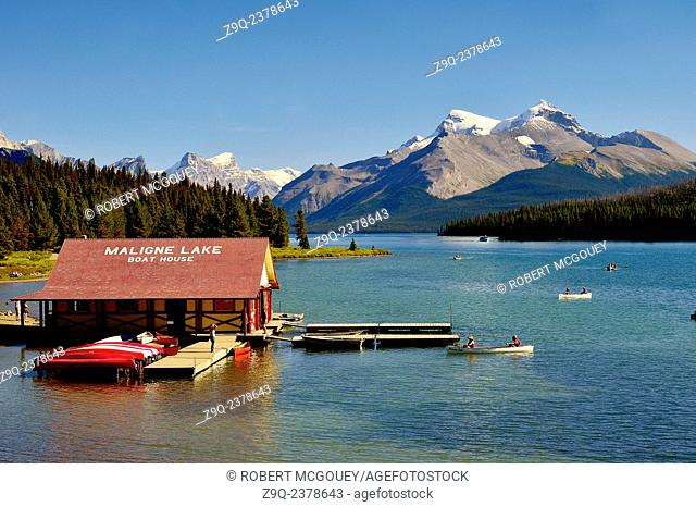 An image of Maligne Lake showing the boat house with people paddeling canoes and the rocky mountains in Jasper National Park Alberta Canada