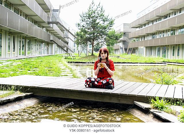 Amsterdam, Netherlands. Young, redhaired woman sitting realy Zen on a closed garden bridge inside her apartment building, while drinking a hot cup of tea