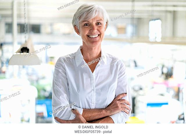 Portrait of smiling senior businesswoman in a factory