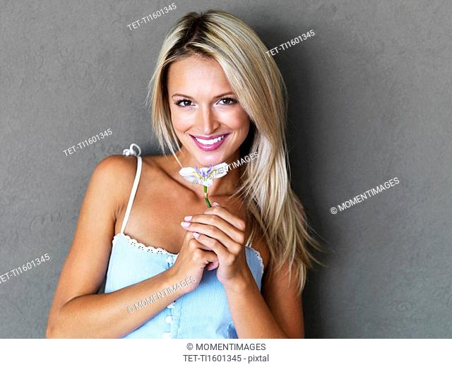 Pretty blond woman holding a flower