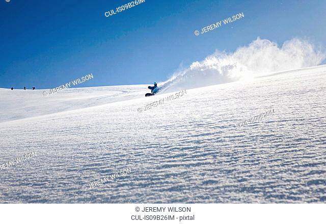 Male snowboarder snowboarding down mountain, Trient, Swiss Alps, Switzerland