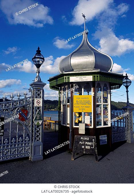 Entrance to Bangor pier. Signs. Railings. Sea in distance