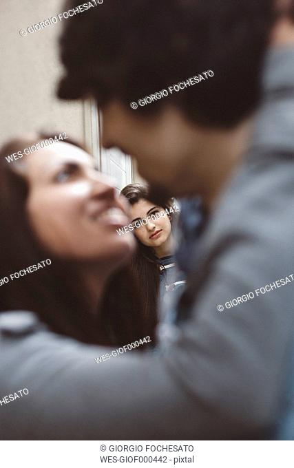 Young couple kissing with another woman looking at them