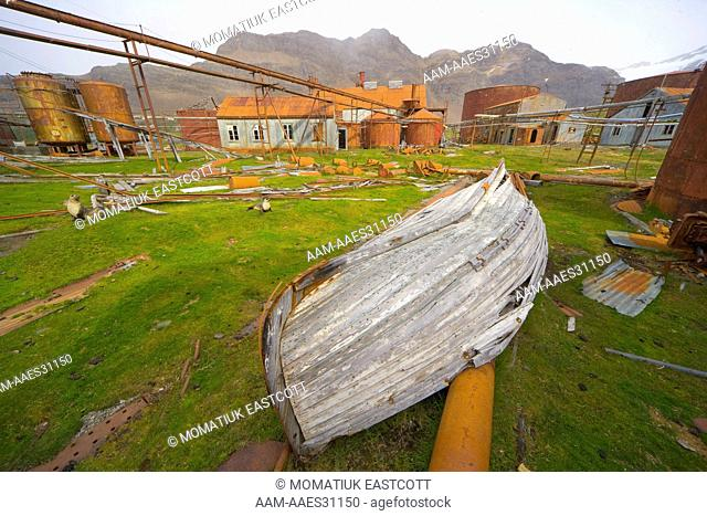 Old boat in abandoned whaling station full of broken machinery, collapsing buildings, barrels, pipes and tanks, Leigh Harbour