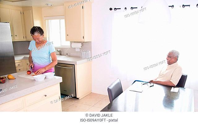 Senior couple at home, man sitting at table while woman prepares fruit salad