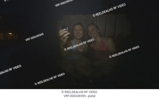 Young women photographing while enjoying steam water in hot tub during winter