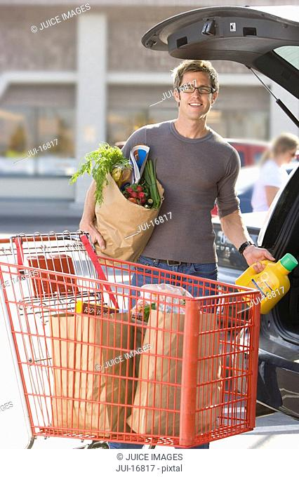 Man loading grocery bags in car