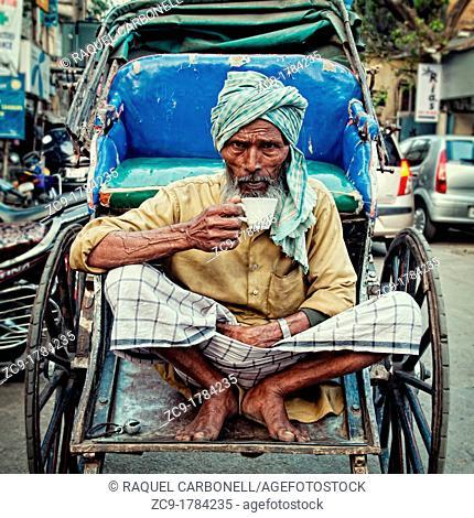 Rickshaw wallah taking a cup of indian tea on his rickshaw  Calcutta, India