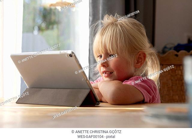 Portrait of blond little girl using digital tablet at home