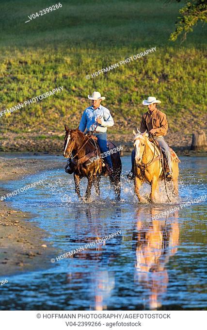 Two wranglers (Cowboys) on horses, riding through water, California, USA