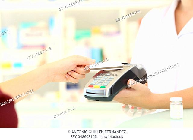 Close up of a customer hands paying with credit card reader in a pharmacy