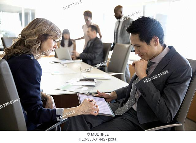 Businessman and businesswoman using digital tablet in conference room meeting
