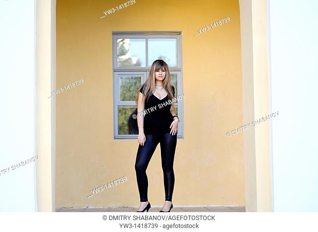Attractive blond 20-25 years girl against ancient window