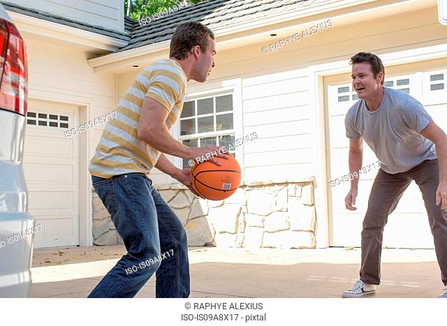 Father and adult son playing basketball
