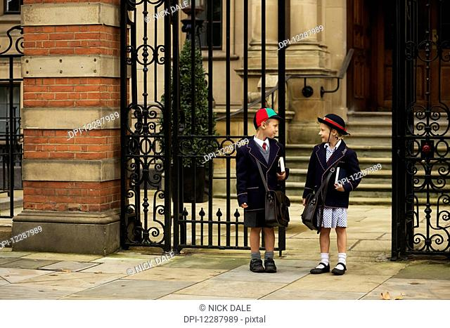 Young boy and girl students in uniform talking outside the school; London, England