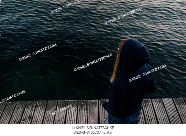Back view of woman wearing hooded jacket standing in front of the sea