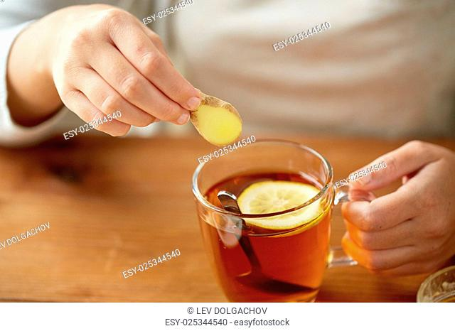 health, traditional medicine and ethnoscience concept - close up of woman adding ginger to tea cup with lemon