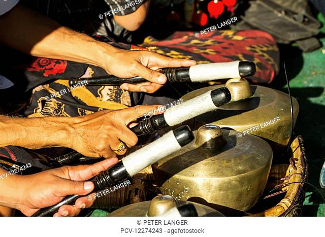 Hands of gamelan musicians playing bonangs during a Ngaben or Cremation Ceremony, Klungkung, Bali, Indonesia