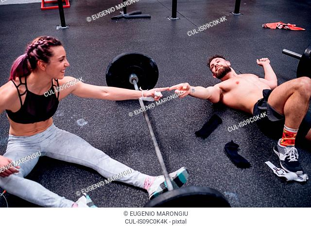 Young woman and man training together, touching fingers over barbell in gym