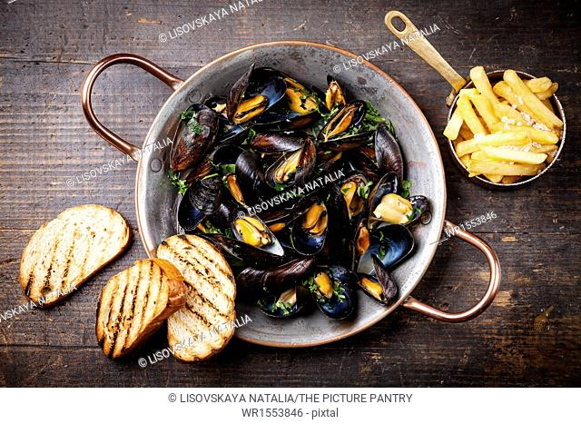 Mussels in copper cooking dish and french fries on dark wooden background