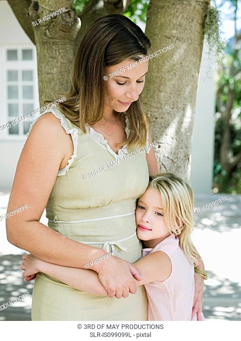 Mother and daughter embracing by tree