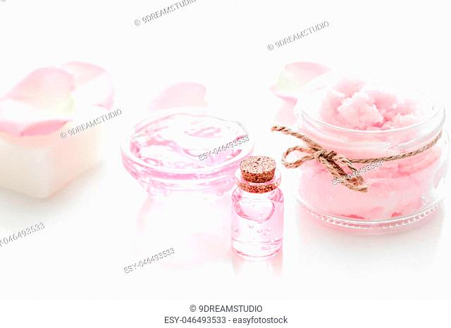 spa set with rose flowers extract and cosmetic for body care on white desk background