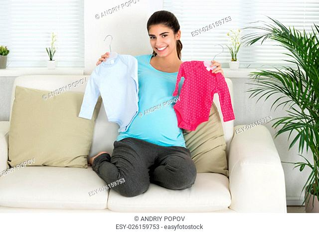 Portrait of happy pregnant woman holding baby clothes while sitting on sofa at home