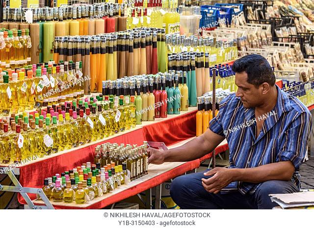 Man setting up market stall of colourful bottles, Campo de' Fiori, Rome, Italy