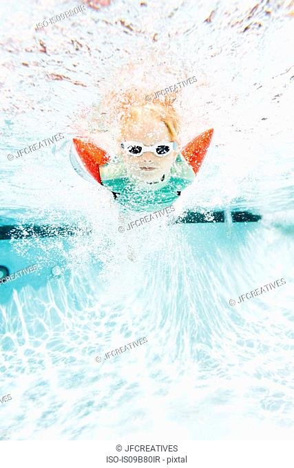 Young boy swimming under water in swimming pool, underwater view