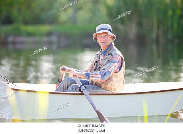 Portrait of smiling senior man fishing in rowboat on sunny lake