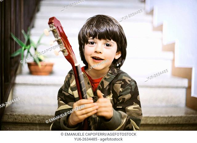 Portrait of little boy sitting on the stairs holding a guitar