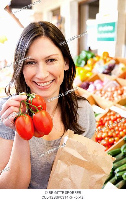 Woman showing fresh tomatoes
