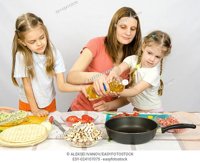 Two little girls at the kitchen table with enthusiasm to help my mother to pour vegetable oil in a frying pan