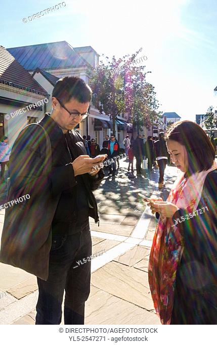 Paris, France, Chinese Couple Tourists Shopping in Luxury Stores in La Vallee Village, Discount Shops, Iphone M.R