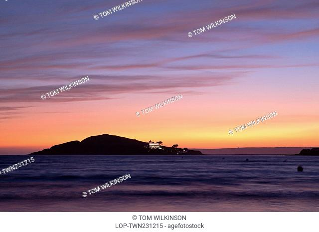 England, Devon, Bantham Beach. View from Bantham Beach towards Burgh Island silhouetted at sunset