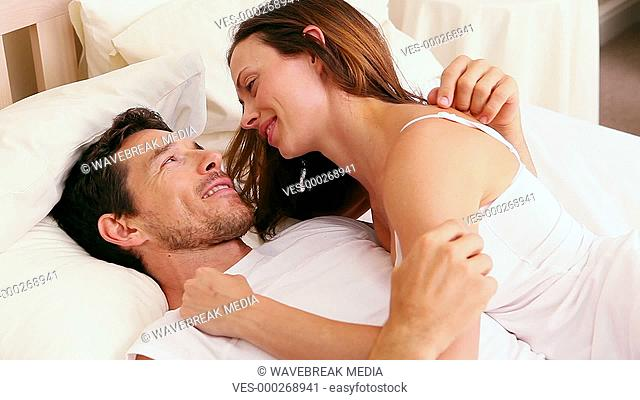 Affectionate couple lying on bed together